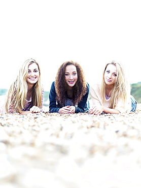Three cheerfully smiling friends lying on a rocky beach