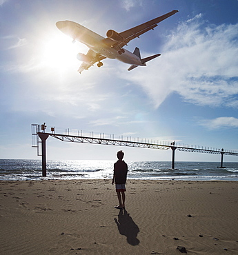 Boy looking up at airplane flying low over ocean near Lanzarote Airport, Puerto del Carmen, Spain
