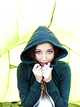 A teenage girl sitting in a tent pulling the sides of her hood sweatshirt together