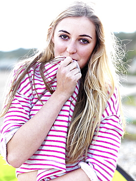 A young woman covering her mouth with her shirt and smiling playfully