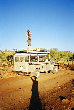 A woman taking a picture on top of an off-road vehicle, Australia
