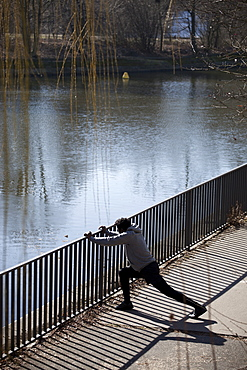 A man doing a stretching lunge against a railing near a river