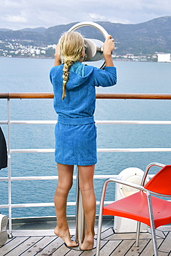 Curious girl on cruise ship looking through viewfinder at ocean