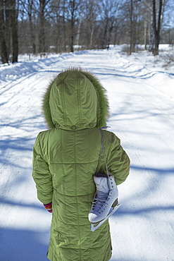 A young girl standing on a snowy road with an ice skate slung over her shoulder