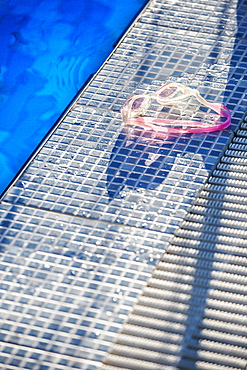 Sunlight shining on a pair of swimming goggles on the edge of a swimming pool