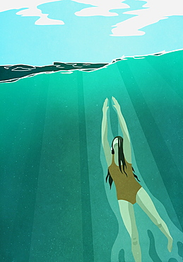 Woman swimming, ascending to ocean surface