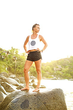 Portrait confident, fit young woman standing on ocean rock, Sayulita, Nayarit, Mexico