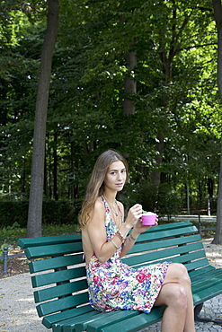 Young woman holding ice cream sitting on park bench, portrait