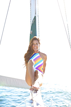 Portrait confident woman in bathing suit on sunny sailboat