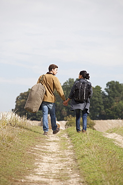 Young couple holding hands and walking through dirt track