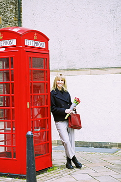 Woman with bunch of tulips leaning against red telephone box