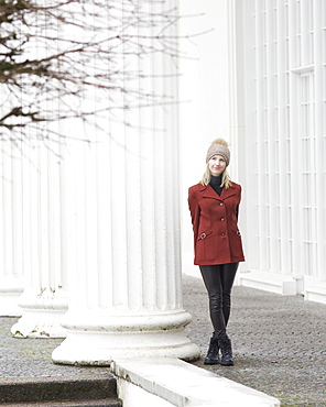 Portrait serene woman in coat and knit hat standing at column