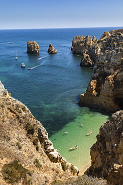 Aerial view tourists boating along ocean cliffs, Lagos, Algarve, Portugal