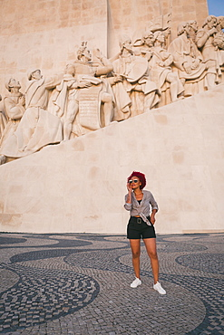 Stylish woman in sunglasses below Monument to the Discoveries, Lisbon, Portugal