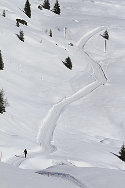 Cross country skier on snow covered mountain path, Vals, Canton of Grisons, Switzerland