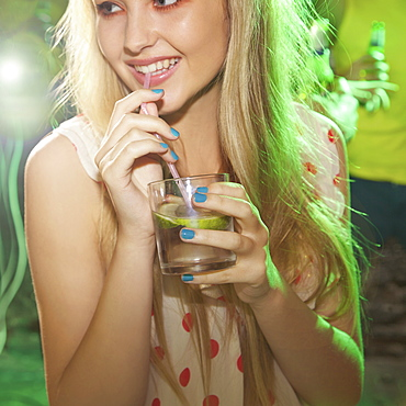 Happy teenage girl drinking at party