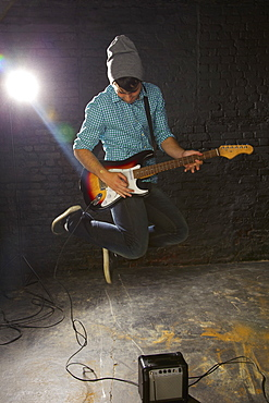 Teenage boy playing electric guitar, jumping above amplifier