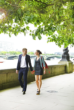 Happy young couple holding hands and walking along Thames River, London