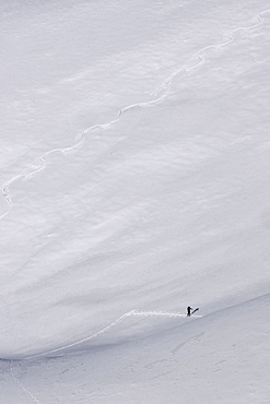 Distant hiker on steep mountain ski slope, Brixen, South Tyrol, Italy