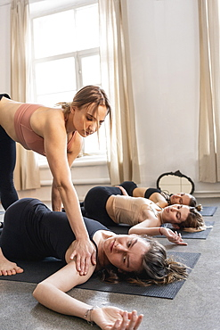 Yoga instructor adjusting student in supine spinal twist