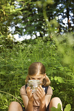 Curious girl with insect jar in woods