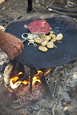 Detail of a man cooking food over a campfire