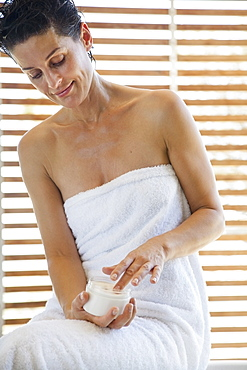 Woman in towel applying moisturiser in bathroom