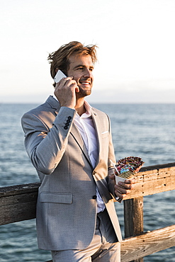 Businessman with ice cream cone talking on smart phone on ocean pier