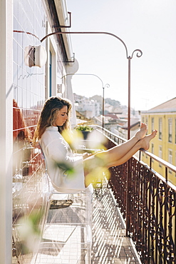 Young woman relaxing on sunny apartment balcony, Lisbon, Portugal