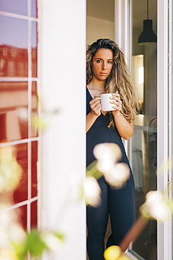Portrait young woman drinking tea in patio doorway