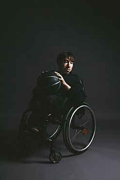 Male paraplegic athlete with basketball in wheelchair