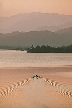 Rowboat on tranquil lake at sunset, Whiskeytown Lake, Redding, California, USA