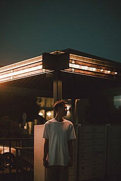 Young man standing below illuminated awning