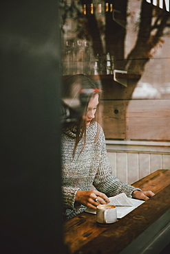 Young woman reading book and drinking espresso at cafe window