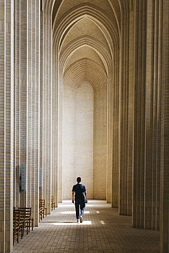 Young man walking along cloister, Grundtvigs Church, Copenhagen, Denmark