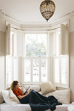 Young woman relaxing on living room sofa reading book in bay window