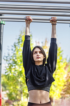 Fit young woman hanging from monkey bars at playground