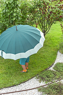 Toddler under large green umbrella in garden