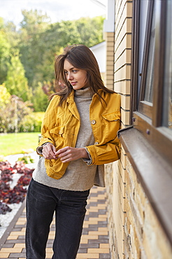 Beautiful young woman in yellow jacket outside house
