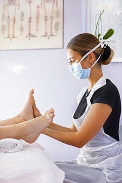 Female masseuse in face mask massaging woman's feet in spa