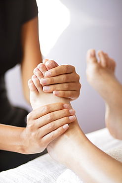 Close up female masseuse massaging client's feet