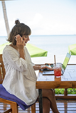 Woman with smart phone and laptop working at beach cafe table