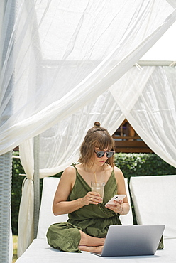 Woman with cocktail using smart phone and laptop in cabana