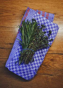 Fresh rosemary and thyme herb bunch on kitchen towel