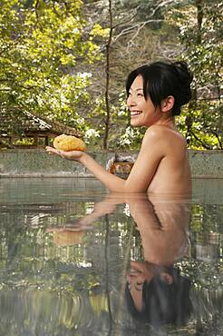 Happy young woman with loofah sponge in pool at Onsen