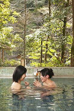 Happy young women friends soaking in water at Onsen spa