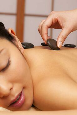 Close up young woman receiving hot stone massage - 1177-4220