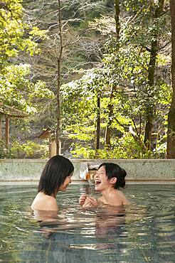 Happy young women friends laughing in soaking pool at Onsen
