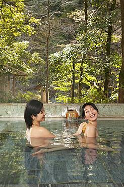 Young woman with loofah scrubbing friend's back in pool at Onsen