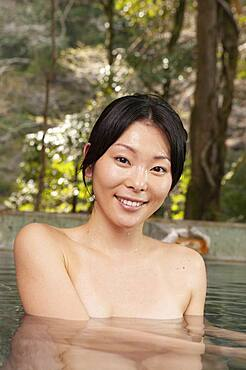 Portrait beautiful young woman soaking in pool at Onsen
